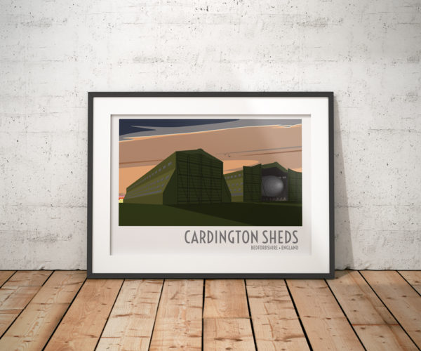 A photo of a framed copy of my modern travel poster of the airship sheds at Cardington Airfield, a former Royal Air Force station in Bedfordshire, England.
