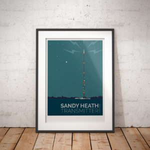 A photo of a framed copy of my modern travel poster of a moonlit Sandy Heath transmitting station, a television broadcast station located between the towns of Sandy and Potton, Bedfordshire.