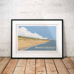 A photo of a framed copy of my modern travel poster of beautiful Brancaster Beach on the north coast of the English county of Norfolk.