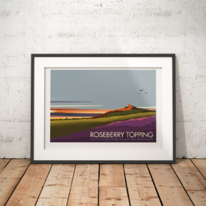 A photo of a framed copy of my modern travel poster of Roseberry Topping, a distinctive hill in North Yorkshire, England. It is situated near Great Ayton and Newton under Roseberry. Its summit has a distinctive half-cone shape with a jagged cliff.