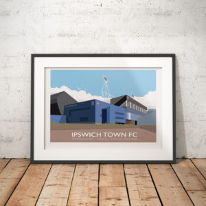 A photo of a framed copy of my modern travel poster of Portman Road football ground, Ipswich, Suffolk, the home of Ipswich Town FC since 1884.