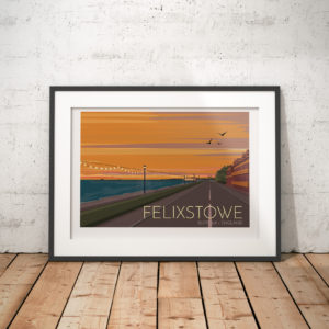 A photo of a framed copy of my modern travel poster of the sun setting over the town of Felixstowe with the cranes of the container port and tankers on the horizon.