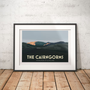 A photo of a framed copy of my modern travel poster of The Cairngorms, a mountain range and national park in the eastern Highlands of Scotland.