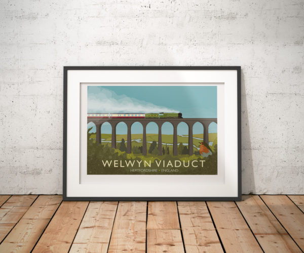 A photo of a framed copy of my modern travel poster of of the Flying Scotsman crossing the Welwyn Viaduct in Hertfordshire.