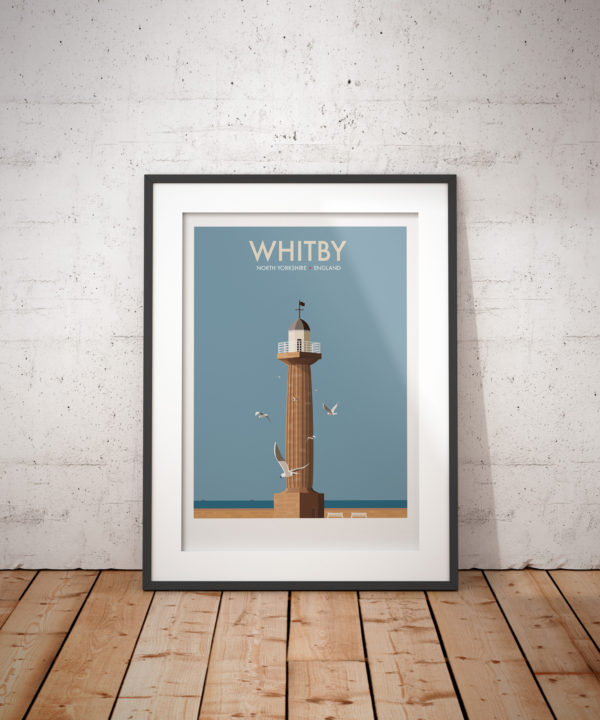 A photo of a framed copy of my modern travel poster of Whitby's 19th century West Pier Lighthouse.