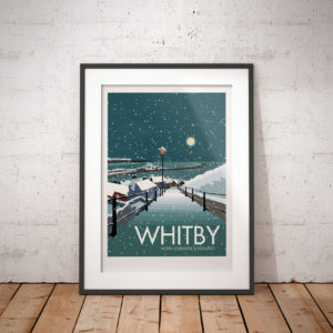 A photo of a framed copy of my modern travel poster of a moonlight view of a snowy Whitby harbour, on the North East coast of England.